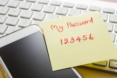 Easy number password note stick on smartphone, keyboard. Easy number password handwriting on yellow paper note stick on blank black screen of smartphone with stock photos