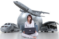 Easy online travel planning. Young woman sitting on the floor with a laptop with an international tourism background Royalty Free Stock Photography
