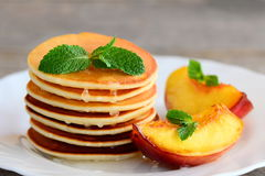 Everyday pancakes with syrup and grilled fruit on a serving plate. Pancake recipe without baking powder. Breakfast idea. Easy pancake recipe without baking Stock Image