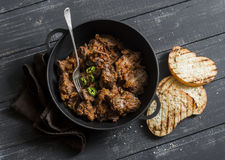Easy peri-peri chicken livers in a cast iron skillet on a dark background, top view. royalty free stock image