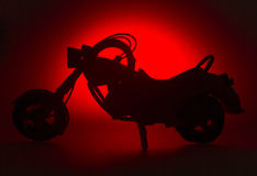 Easy rider. Silhouette of a motorbike model on a red background Stock Photography