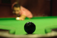 Easy shot. Close-up of snooker black ball next to a pocket, waiting to be potted by player in the background Stock Photos