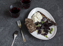 Easy snack - baked beetroot, goat's cheese and red wine. On a dark background Royalty Free Stock Image