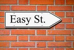 Easy street signpost wall bricks. Easy street signpost on wall of bricks Stock Photos