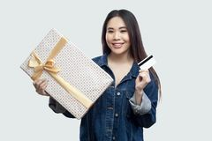 Easy to buy with online shopping! Satisfied young asian girl in blue denim jacket standing and holding present with yellow bow and. Bank card, looking at camera royalty free stock photos