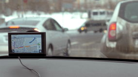 Easy traveling in the city with GPS device. MOSCOW, RUSSIA - FEBRUARY 2, 2015: Car in the city stopping at traffic lights and starting moving. View through stock footage