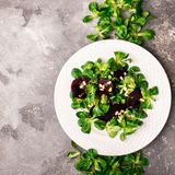 Easy vegetarian salad with fresh vegetables and young greens on white dish. The concept of healthy and proper nutrition. royalty free stock image