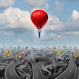 Easy Way Forward. Rise above confusion leadership concept with a businessman in a balloon flying and soaring over a complicated group of roads as a business Royalty Free Stock Image