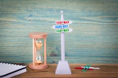 Easy way and Hard Way. Signpost on wooden table royalty free stock image