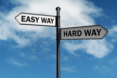 Easy way and hard way road sign. Crossroad signpost saying easy way and hard way concept for choice, confusion or decisions royalty free stock photo