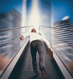 Easy way to success. Concept of Easy way to success with businessman and escalator stock photography