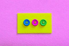 Easy ways to sew buttons to felt. Yellow felt piece with colourful buttons isolated on pink felt background. How to sew a button by hand. Best way to stitch a Royalty Free Stock Photos