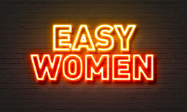 Easy women neon sign on brick wall background. Stock Image
