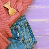 Easy womens casual clothes idea. Stylish blue jeans, knit pink sweater, hair grip on a purple wooden background with empty place. Cute casual outfit. Casual royalty free stock images