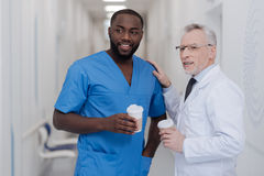 Easygoing aged practitioner enjoying conversation with young colleague at work stock photos