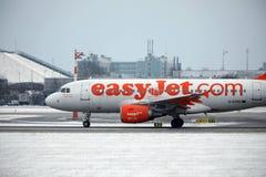 EasyJet离开从多雪的跑道的空中客车A319-100 G-EZDD 免版税库存照片