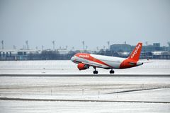 EasyJet离开从多雪的跑道的空中客车A319-100 G-EZDD 库存图片