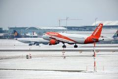 EasyJet离开从多雪的跑道的空中客车A320-200 G-EZUJ 库存照片