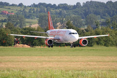 Easyjet Airbus A319. JULY 2009, CRACOV BALICE AIRPORT. Easyjet Airbus A319 just before takeoff roll. In the upper left church founded in 1603 on the top of the stock image
