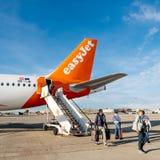 EasyJet Airbus A320-214 OE-IJR aircraft on tarmac airport people. BASEL, SWITZERLAND - NOV 11, 2018: EasyJet Airbus A320-214 OE-IJR aircraft on tarmac with stock photography