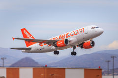 Easyjet Airbus A319 take-off. An Easyjet Airbus A319 is taking off from Malaga Airport, mountains in the background stock image