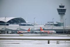 EasyJet and Alitalia planes at terminal gates in Munich Airport, snow. On runway, control tower stock images