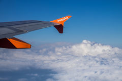 EasyJet company logo on aircraft winglet on blue sky and clouds Royalty Free Stock Photography