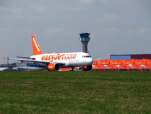 Easyjet and control tower. Airbus a 319-111 low cost airlines Easyjet taxi to the runway on the London Luton Airport royalty free stock photo