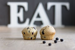 Eat. Blueberry muffins / cupcakes on a kitchen counter with wooden letters EAT in the background Stock Photos