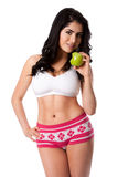 Eat an apple to stay fit. Beautiful happy young woman fit slim in shape with apple for good health standing showing abs and body, weight conscious diet nutrition Royalty Free Stock Image