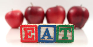 Eat Apples. Wooden blocks spelling the word Eat with apples in the background Stock Photography
