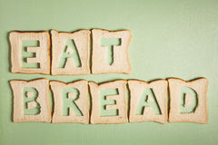 Eat bread text carved out of white bread slices Royalty Free Stock Image