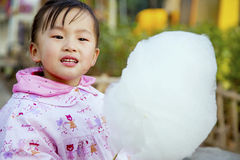 Eat the Chinese female of cotton candy. Chinese woman eating cotton candy in the park Royalty Free Stock Image