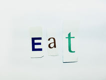 Eat - Cutout Words Collage Of Mixed Magazine Letters with White Background. Caption composed with letters torn from magazines with White Background Stock Photos