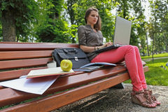 Eat Fresh While Studying. Young woman studying outside in a park on a bench.The focus is selective on the bitten apple Stock Photo
