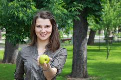 Eat Fresh. Young smiling woman offering a green apple outside in a park in summer Stock Photo