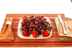 Eat Fruit. Concept: Eat more fruit. Plate piled high with red grapes, accented with strawberries, napkins, fork, and table accessories Stock Images