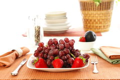 Eat Fruit. Concept: Eat more fruit. Plate piled high with red grapes, accented with strawberries, napkins, fork, and table accessories Royalty Free Stock Images