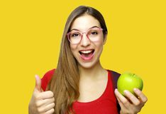 Eat fruits every day. Close up isolated studio portrait of young cheerful girl with long hair in red t-shirt smiling, showing stock photos