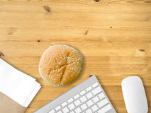 Eat junk and work. Eating hamburger junk food on work desk Royalty Free Stock Images