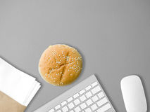 Eat junk and work. Eating hamburger junk food on work desk Stock Photos