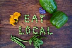 """""""Eat Localâ€- Phrase gemacht von den grünen Erbsen auf hölzernem Hintergrund stockbild"""