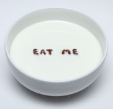 Eat me. Words eat me to float inside soup plate of milk Stock Photo