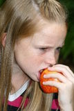 Eat me. A white caucasian girl child eating an apple Royalty Free Stock Photo
