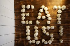 Eat me. Letters from dumplings on dark and light boards. stock images