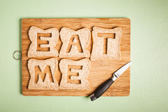 Eat me text carved out of brown bread slices Royalty Free Stock Image