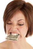 Eat money. A woman with money in her mouth with a upset expression on her face Royalty Free Stock Images