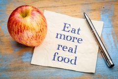 Eat more real food reminder note. Eat more real food reminder - handwriting on a napkin with a fresh apple stock images