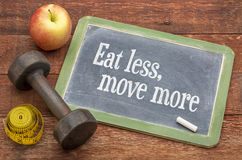 Eat less, move more concept. Eat less, move more fitness and healthy living concept - slate blackboard sign against weathered red painted barn wood with a stock photography