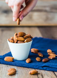 Eat nuts, almonds hands of white cup Stock Image